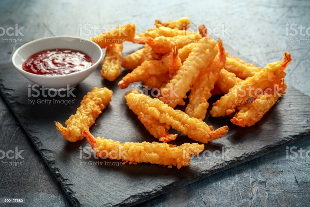 Fried Shrimps tempura with sweet chili sauce on black board stone