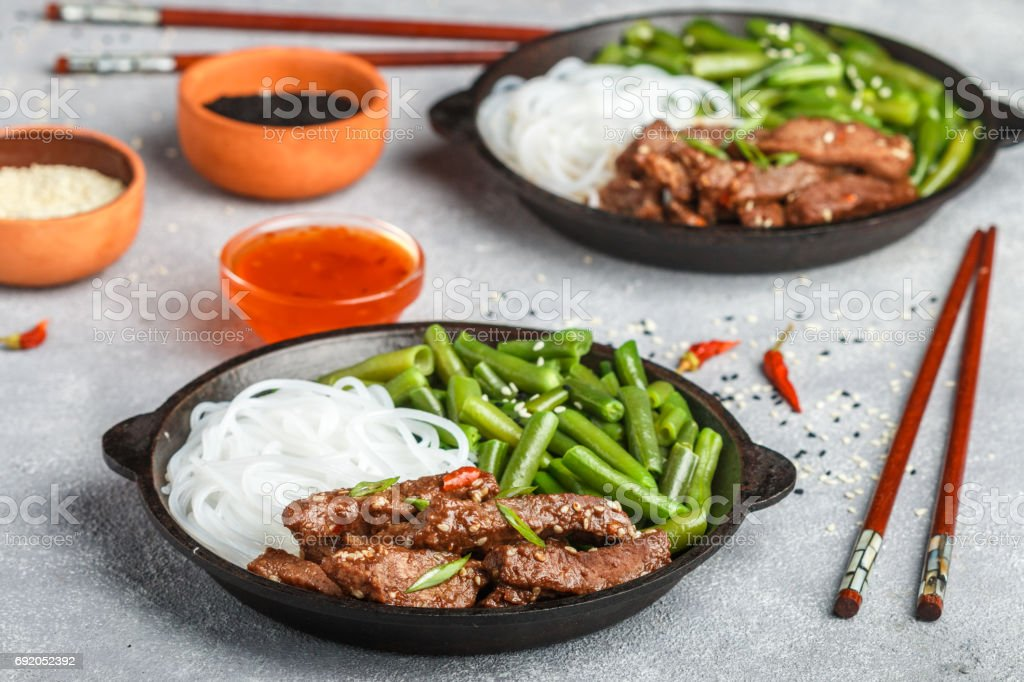 Fried spicy beef with sesame seeds, green beans and rice noodles. Dinner in the Asian style. Selective focus stock photo