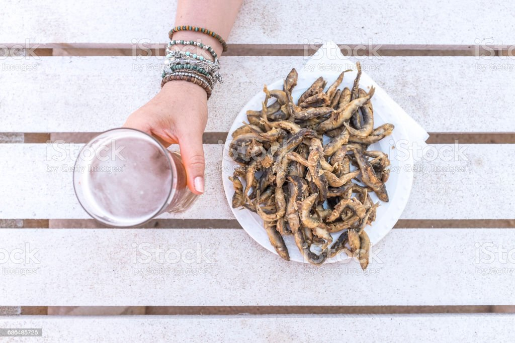 Fried sprat fish and cold glass of beer stock photo