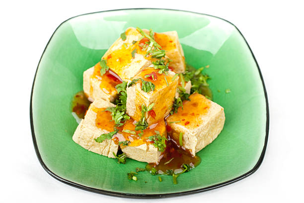Fried squares of tofu served on green ceramic plate stock photo