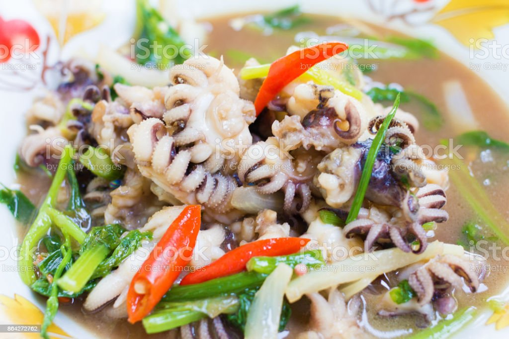 Fried squid pepper onion and parsley plate on the wood. royalty-free stock photo