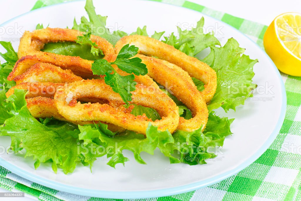 Fried Squid Rings in Breadcrumbs with Lettuce and Lemon stock photo