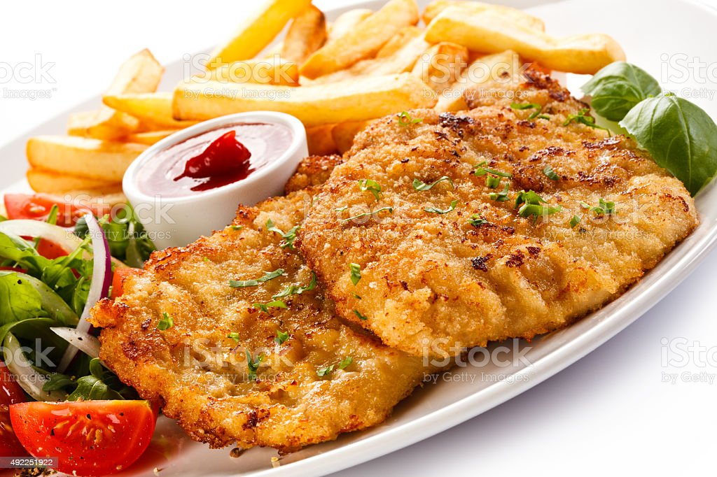 Fried steaks, French fries and vegetables stock photo