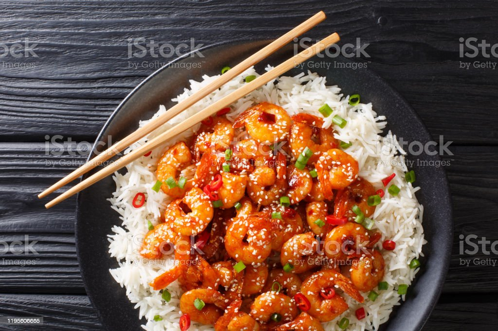 Fried sticky shrimps with garlic, chilli, sesame seeds and green onions served with rice close-up in a plate. Horizontal top view Fried sticky shrimps with garlic, chilli, sesame seeds and green onions served with rice close-up in a plate on a table. horizontal top view from above Above Stock Photo