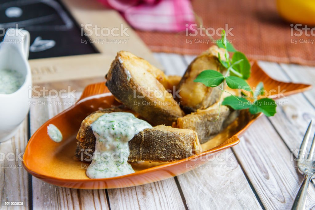 Fried tench with sauce on a beautiful ceramic plate stock photo