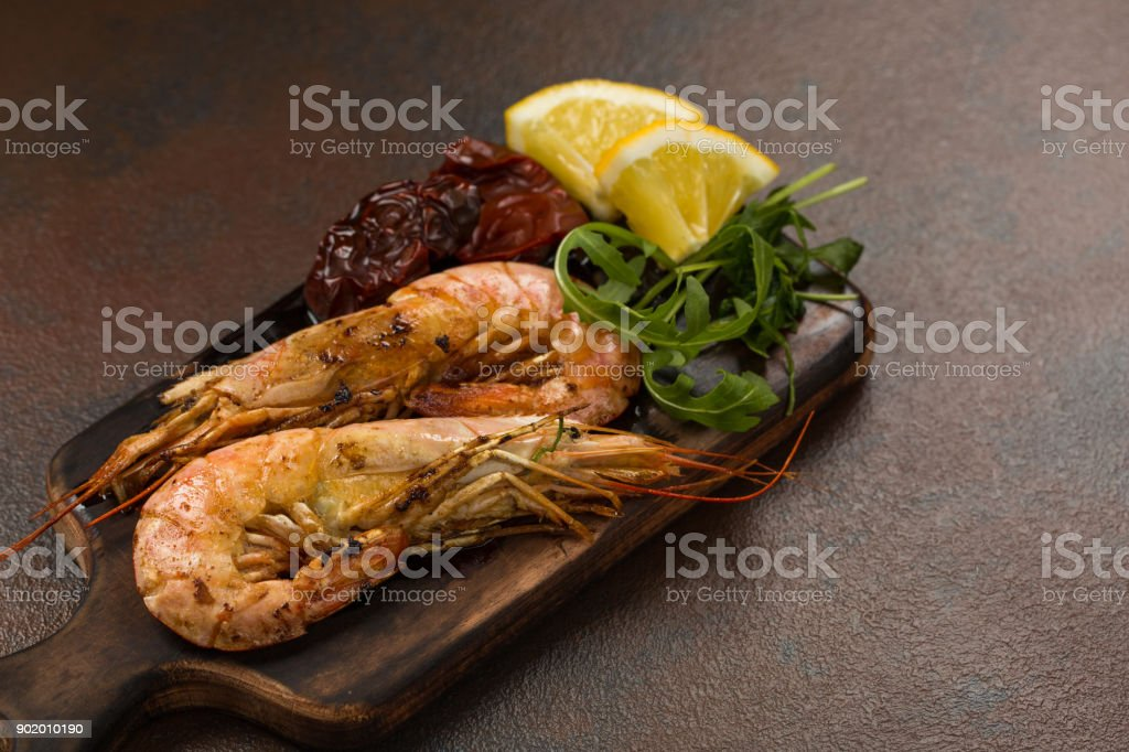 Fried tiger shrimps or langostinos with lemon, arugula, sun dried tomatos on a dark wooden cutting board. Placed on a background of dark table stock photo