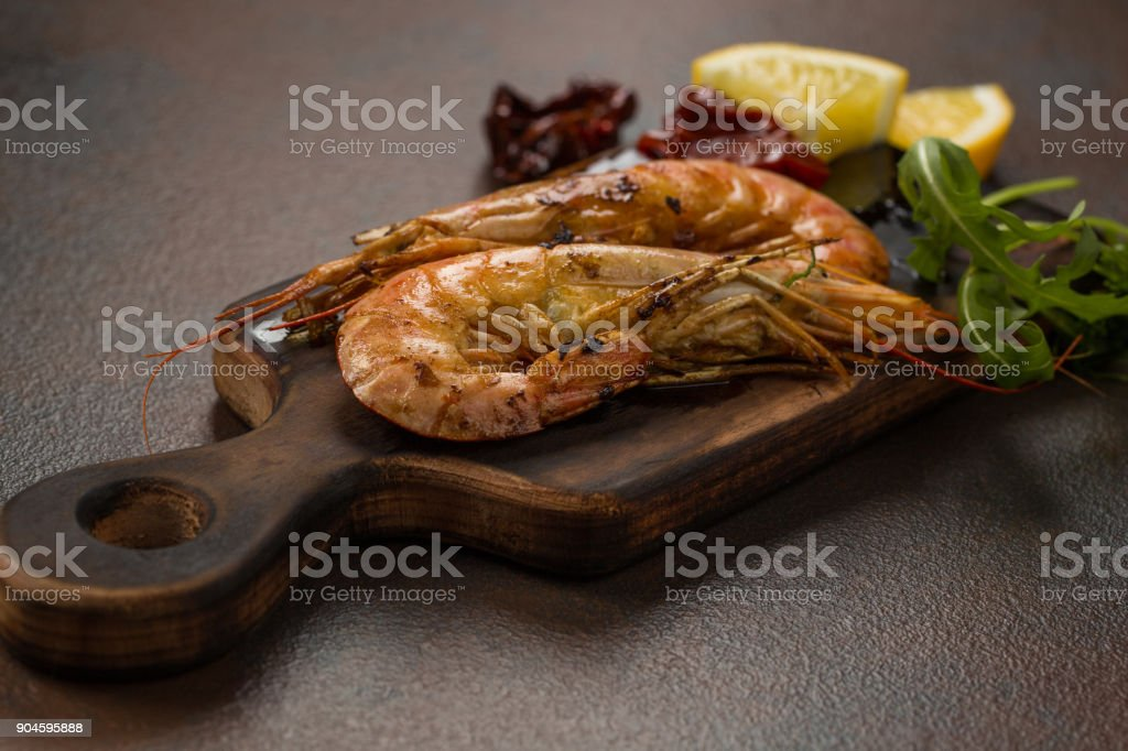 Fried tiger shrimps with lemon, sun-dried tomatoes and greens or rukkola on a dark wooden cutting board. stock photo