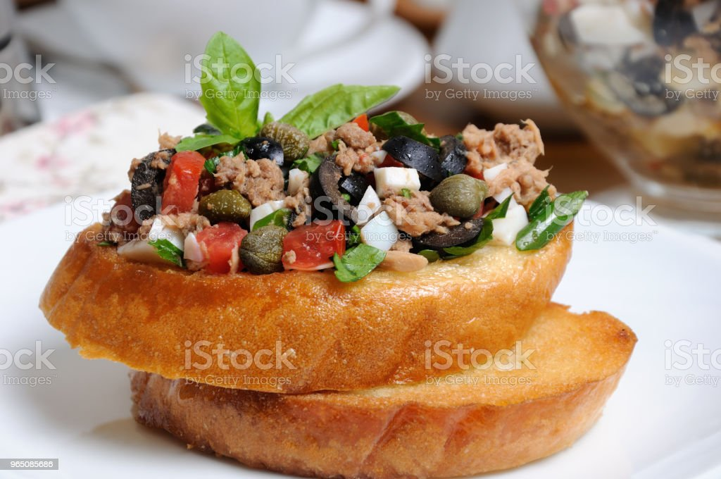Fried toast with chopped tuna with egg, cubes of tomatoes and olive slices, capers zbiór zdjęć royalty-free