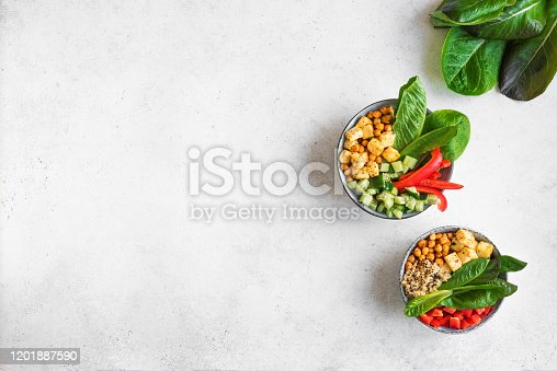 Fried Tofu Salad with Cucumbers, Fried Chickpeas, Leaves vegetables and Sesame Seeds. Balanced vegan colorful salad for healthy lunch in ceramic bowl, top view, copy space.