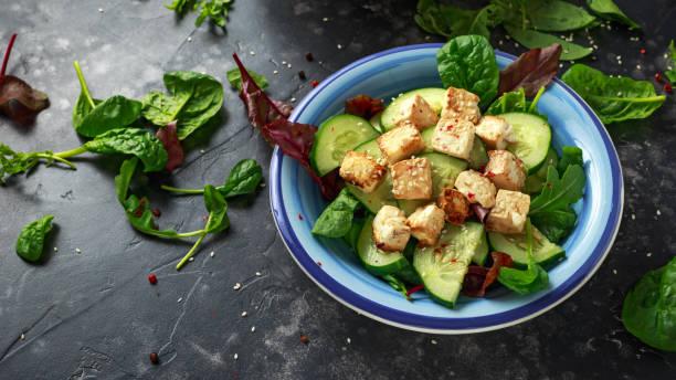 Salade de Tofu frit avec concombres, graines de sésame et légumes verts - Photo