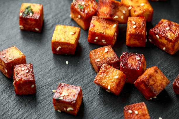 Fried Tofu with chopstick and sesame seeds on rustic stone board stock photo