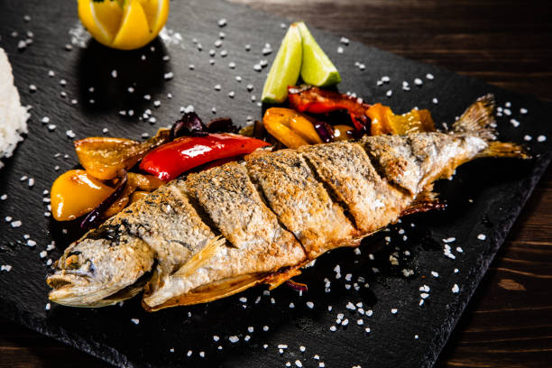 Fried trout with rice and vegetables on wooden background stock photo
