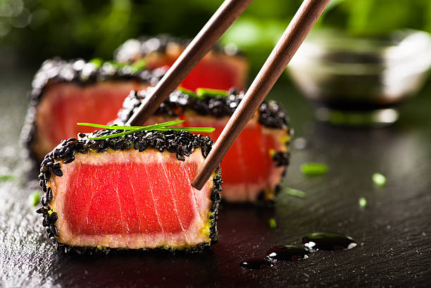 fried tuna steak in black sesame with chopsticks - japanese food stock photos and pictures