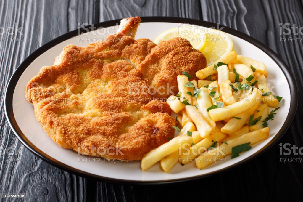 Fried veal cutlet Milanese with lemon and French fries close-up on a plate. Horizontal stock photo