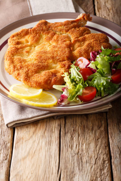 fried veal cutlet milanese with lemon and fresh salad of tomatoes and lettuce close-up on a table. vertical - escalope imagens e fotografias de stock