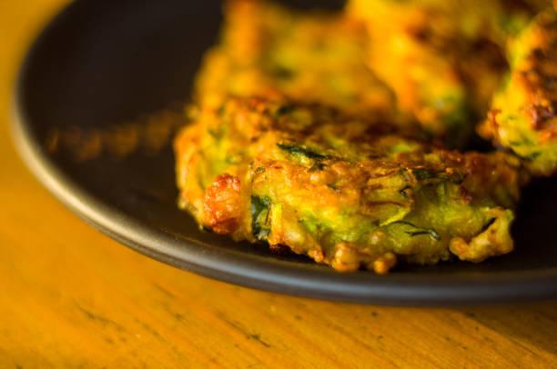 gebratene gemüse krapfen mit zucchini, möhren, kräutern, eiern und käse. - käse zucchini backen stock-fotos und bilder