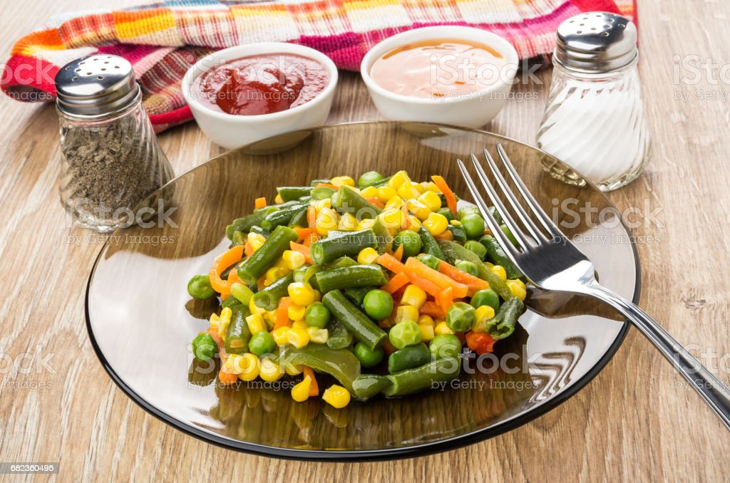 Fried vegetable mix and fork in plate, sauces in bowls foto stock royalty-free
