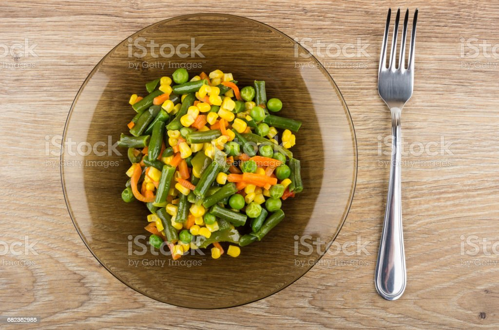 Fried vegetable mix in brown transparent plate and fork foto stock royalty-free