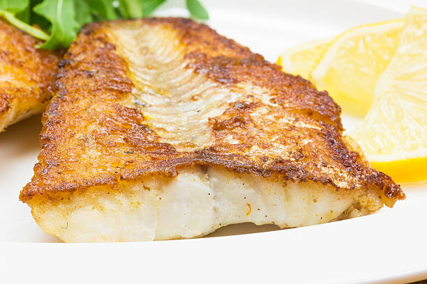 Fried white fish White fish with lemon on white plate, selective focus perch fish stock pictures, royalty-free photos & images