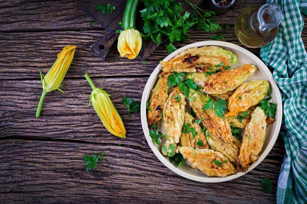 Fried zucchini flowers stuffed with ricotta and green herbs. Vegan food. Italian cuisine. Top view stock photo