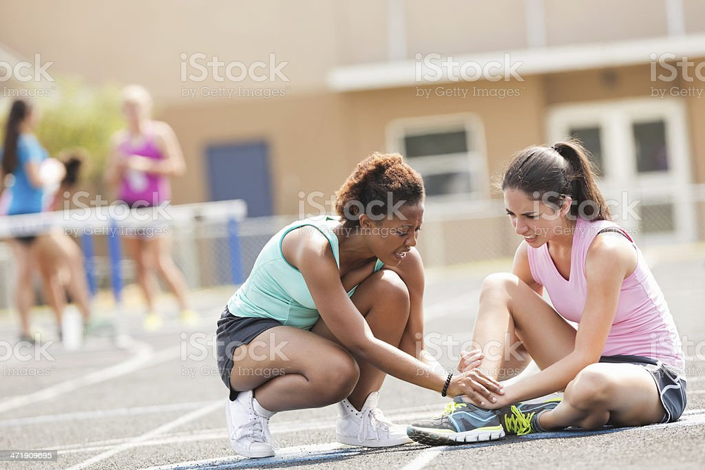 Friend checking on injured athlete during track meet race stock photo