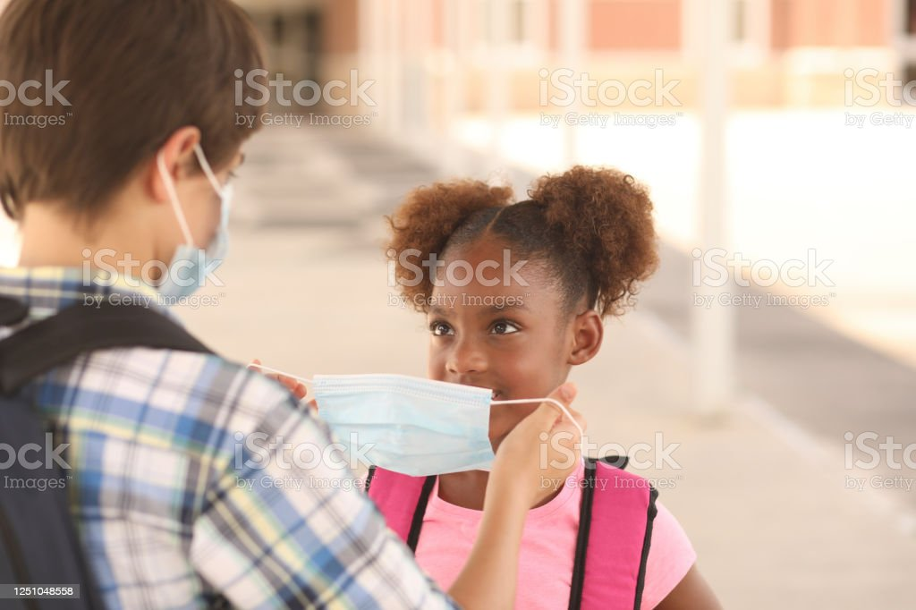 Friend helps younger student put on protective face mask. COVID-19. Back to school. Latin and African descent friends on school campus. Older student helps younger student put her mask on before going to class.  School in background.  COVID-19. African Ethnicity Stock Photo