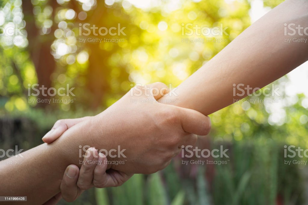 Friend holding hands together at outdoor. Hand holding between...