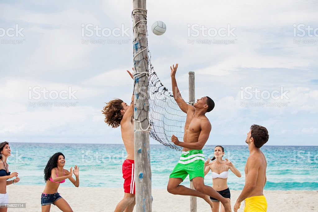 Friend playing volleyball on the beach stock photo
