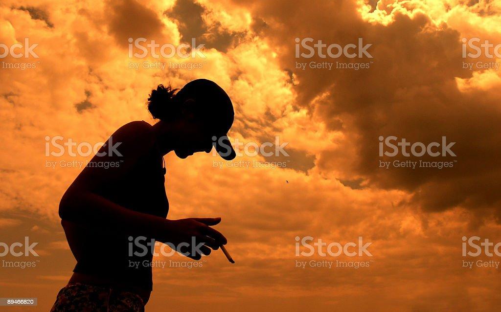 friend smoking on a dramatic sephia sky royalty-free stock photo