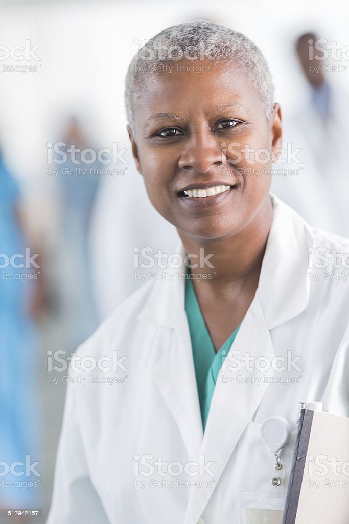 Friendly African American female doctor smiling in busy hospital stock photo