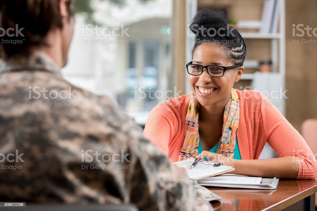 Friendly African American female military counselor talks with veteran stock photo