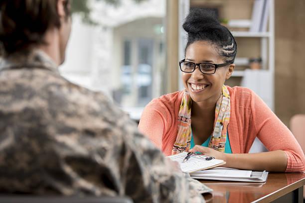 friendly african american female military counselor talks with veteran - séance de psychothérapie photos et images de collection