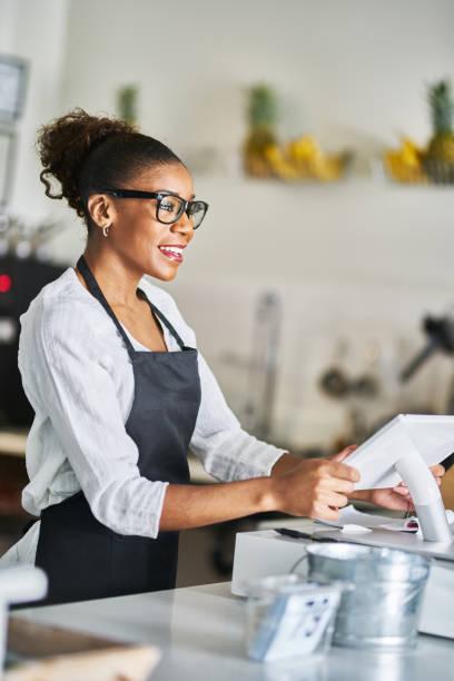 Freundliche afrikanische amerikanische Verkäuferin, die das pos Terminal nutzt, um Bestellungen im Restaurant einzugeben – Foto