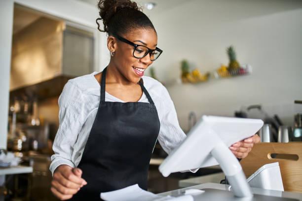 vriendelijke African American Shop Assistant met POS terminal om input orders bij restaurant foto