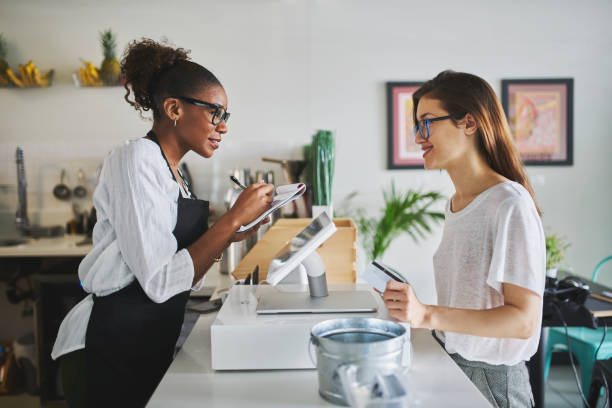 friendly african american waitress taking order on notepad from customer stock photo