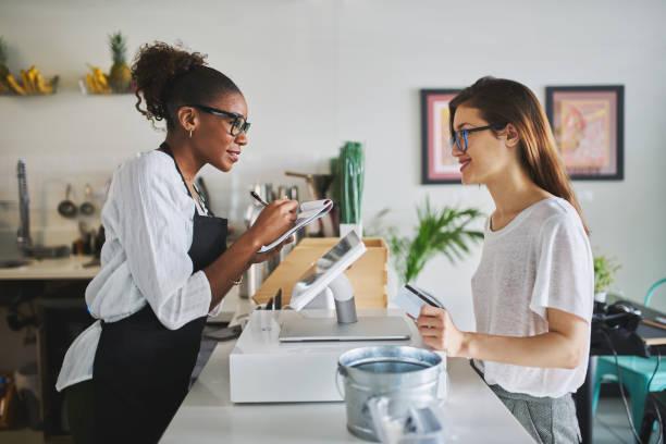 Freundliche afrikanische amerikanische Kellnerin, die auf Notizblock beim Kunden bestellt – Foto