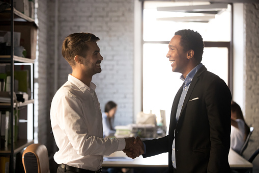 istock Friendly african and caucasian workers handshaking, welcoming new employee concept 1085713992