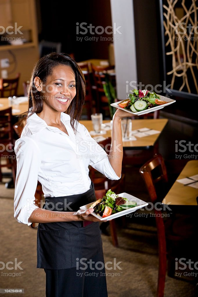 Friendly African-American waitress in restaurant serving food royalty-free stock photo