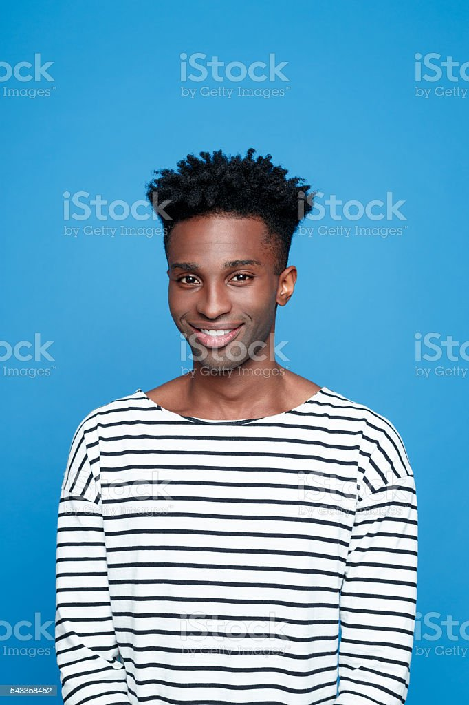 Friendly afro american guy Portrait of happy afro american young man wearing striped top, smiling at camera. Studio portrait, blue background. Adult Stock Photo