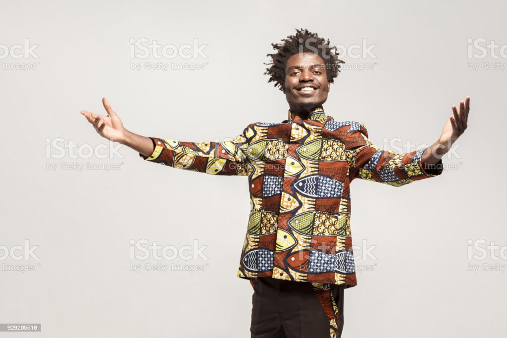 Friendly afro man in traditional clothes toothy smile, say welcome stock photo