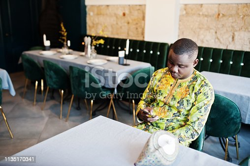 1163696387 istock photo Friendly afro man in traditional yellow clothes at restaurant 1135170341