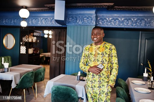 1163696387 istock photo Friendly afro man in traditional yellow clothes at restaurant 1135170346