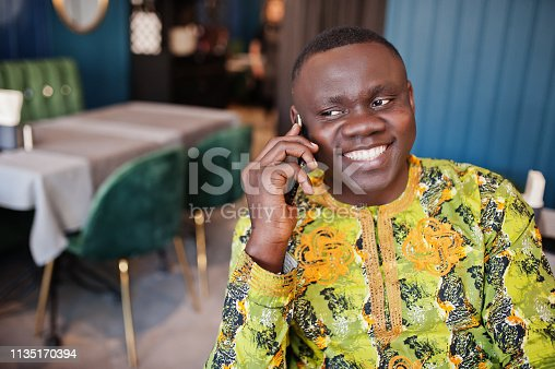 1163696387 istock photo Friendly afro man in traditional yellow clothes at restaurant 1135170394