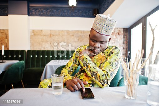 1163696387 istock photo Friendly afro man in traditional yellow clothes at restaurant 1135170441