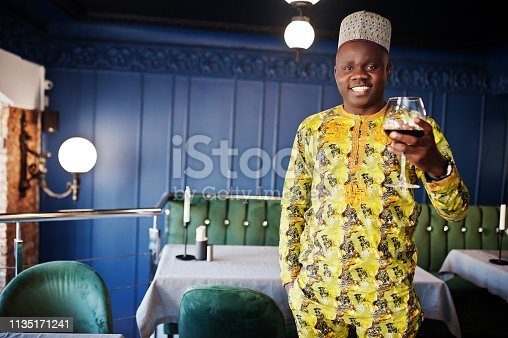 istock Friendly afro man in traditional yellow clothes at restaurant 1135171241