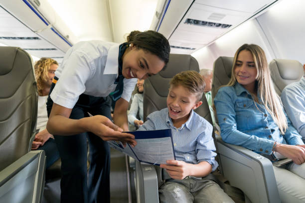 Friendly air hostess helping a boy in an airplane Portrait of a friendly air hostess helping a boy in an airplane and looking very happy - travel concepts. cabin crew stock pictures, royalty-free photos & images