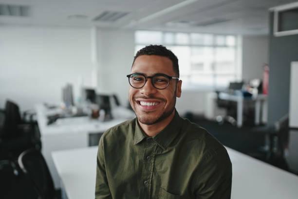 amigable y sonriente joven afroamericano profesional profesional mirando la cámara en la oficina moderna - sólo hombres jóvenes fotografías e imágenes de stock