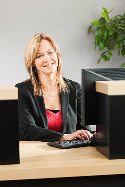 Friendly, Approachable Woman Bank Teller at Retail Banking Customer Counter stock photo