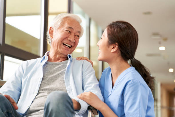 friendly asian caretaker talking to senior patient in nursing home stock photo