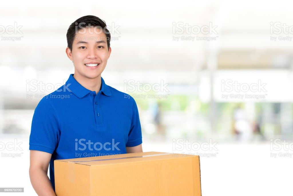 Friendly Asian delivery man in blue polo shirt carrying parcel box - Stock  image .